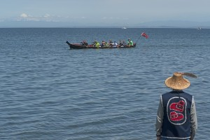 A Suquamish tribal canoe prepares to land at the Jamestown S'Klallam tribe's beach on the Strait of Juan de Fuca on their way to Bella Bella while Jamestown tribal chair, Ron Allen, waits to welcome them.