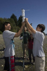 UW professor Danny Grunbaum and CKA teacher Karen Matsumoto oversee two students attach their water sensor computers to a post on a beach near Agate Pass. To view more,  click on the photo.
